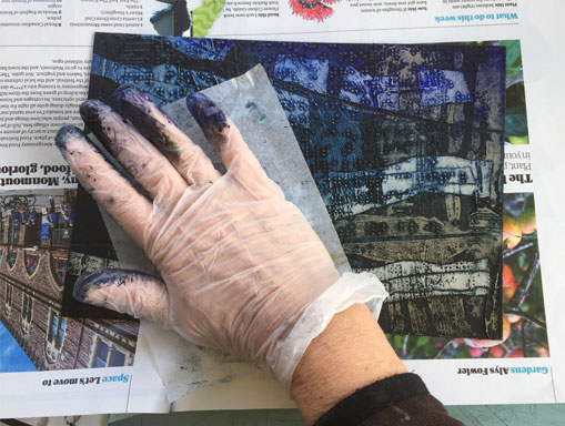 hand wiping Collagraph plate with tissue paper